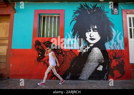 This area is known as La Candelaria, Bogota where there are many murals and graffiti. This work is by female Street Artist ERRE. Young girl tourist. - Stock Photo