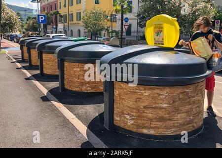 GARDA, ITALY - AUGUST 08, 2019: A man distributes garbage in different containers on the street - Stock Photo