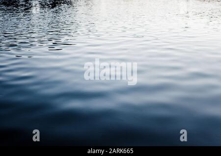 dark and moody water ripples and reflections at sunset - Stock Photo