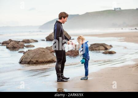 Father and son in wetsuits on beach in New Zealand - Stock Photo