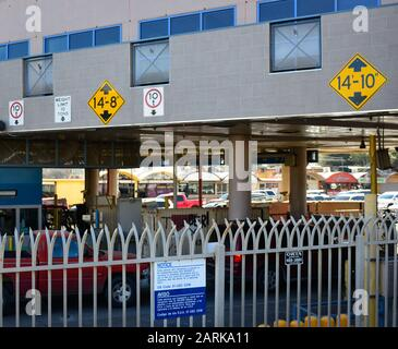 View of metal fence and cars crossing the border into the commercial district of Nogales, MX from Nogales, AZ, USA - Stock Photo