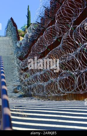 View of US/Mexico metal international border fence with razor wire following uphill between Nogales, AZ, USA and Nogales, Sonora, MX, Stock Photo
