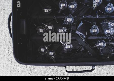 brain drain conceptual still-life, open suitcase with string of lightbulbs symbol of highly trained people moving country to better their life conditi - Stock Photo