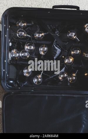 brain drain conceptual still-life, open suitcase with string of lightbulbs switched on symbol of highly trained people moving country to better their - Stock Photo