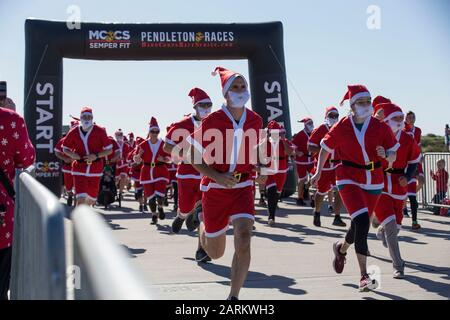 Service members and their families sprint from the starting line during the Santa Run at the Assault Craft Unit 5 compound on Marine Corps Base Camp Pendleton, California, Dec. 15, 2019. The Santa Run is part of the Hard Corps Race Series held by Marine Corps Community Services. MCCS is a comprehensive set of programs that support and enhance the operational readiness, war fighting capabilities, and life quality of Marines, their families, retirees and civilians. (U.S. Marine Corps photo by Lance Cpl. Andrew Cortez) - Stock Photo