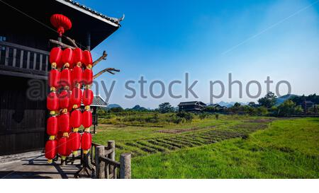 Red lanterns hanging under the eaves of Chinese style house - Stock Photo