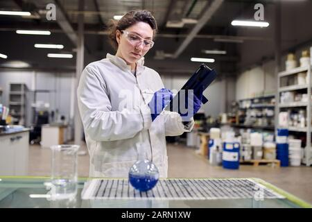 Young woman lab assistant with flask and tablet in hands on blurred background - Stock Photo