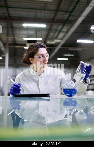 Brunette lab assistant with flask and tablet in hands on blurred background - Stock Photo