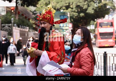 Hong Kong, CHINA. 29th Jan, 2020. A man dressed as Chinese Fairly God of Fortune ( Chai-Sheng ) stand on the street offering 'blessings' to the pedestrians with two masked female assistance during Chinese New Year in Hong Kong under the threat of spreading Coronavirus on Mainland and in overseas.Jan-29, 2020 Hong Kong.ZUMA/Liau Chung-ren Credit: Liau Chung-ren/ZUMA Wire/Alamy Live News - Stock Photo