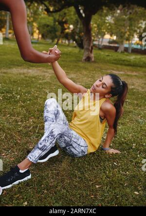 friend helping her friend up after an intense workout session outdoors in the park leaving her exhausted  - Stock Photo