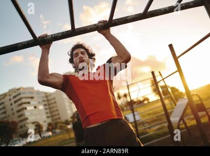 Portrait of a young muscular man listening to music on earphones working out on monkey bars doing pull-ups in outdoor gym