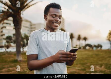 Portrait of a sportive young african american man smiling while texting messages on mobile phone in the park - Stock Photo
