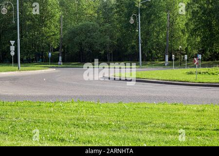 Road for transport with road signs among green grass - Stock Photo