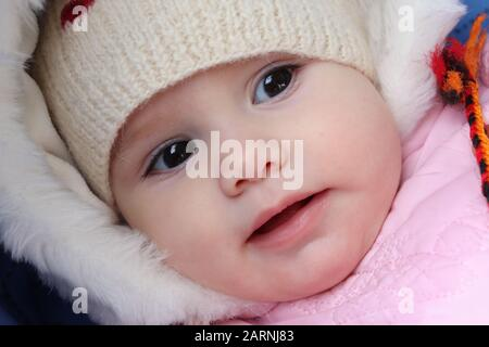 Portrait of a cute 8-month-old baby girl. - Stock Photo