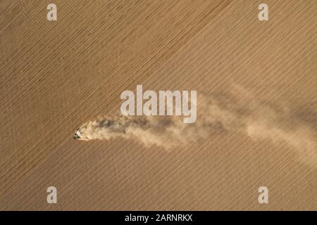 A farmer drives a tractor on a field and creates fine patterns. Brown natural colors give a restful image - Stock Photo