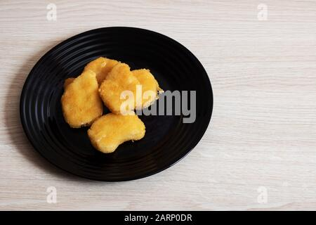 Chicken nuggets on a black plate on a birch table - Stock Photo