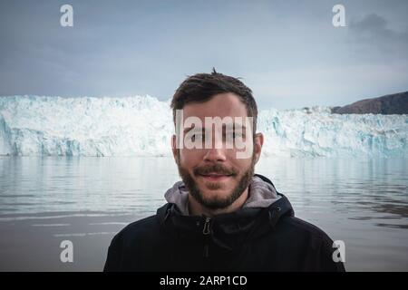 Happy and smiling young man standing in front of Eqip Sermia glacier called Eqi Glacier. Tourist with huge wall of ice in background. The concept of - Stock Photo