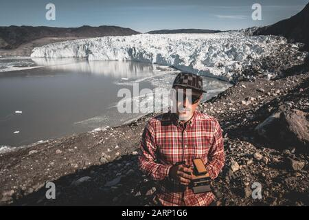 A young man standing in front of Eqip Sermia glacier called Eqi Glacier. Tourist holding an old analogue camera. Wall of ice in background. The - Stock Photo