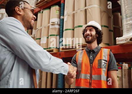 Young partners congratulating each other on new business deal while standing in a modern factory
