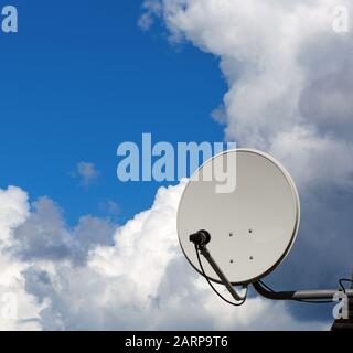 Satellite dish antenna with blue sky with clouds. - Stock Photo