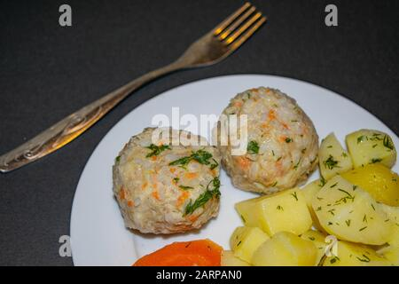 Two meat meatballs with boiled potatoes and boiled carrots on a white plate with a fork on a dark background. Close up - Stock Photo