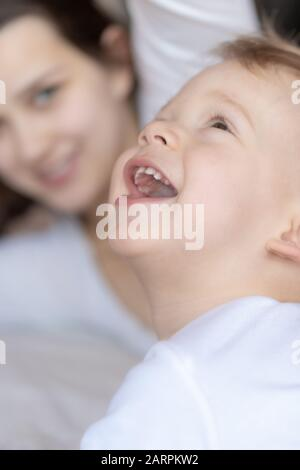 Croon-plan toddler in white looks up and smiles in front of mother