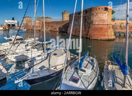 Sailboats at port, car ferry in distance, bastions of Fortezza Vecchia (Old Fortress), medieval fort in Livorno, Tuscany, Italy - Stock Photo