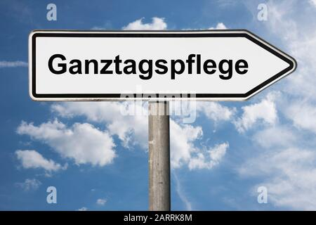 Detail photo of a signpost with the inscription Ganztagspflege (Full day care) - Stock Photo