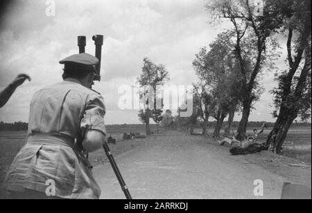 Foreign Military Observers Semarang  Semarang: Visit foreign military observers to the V-Brigade. The company consisting of Servais, Morizon and Sands visited the demarcation line, 3 km past Gombong. Sands takes a look at the roadblocks with the viewer. Date: 28 September 1947 Location: Indonesia, Java, Dutch East Indies, Semarang - Stock Photo