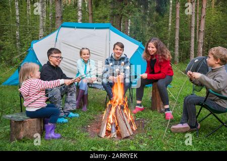 Six children of different age sitting together around burning bonfire having fun roasting marshmallows while camping in a summer forest. Camping tents - Stock Photo