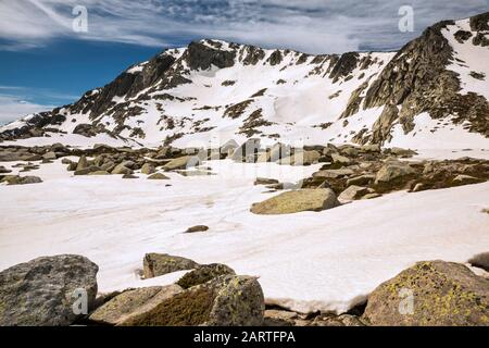 Monte Renoso summit over snow field, melting in mid-May, frozen Lac de Bastiani in distance, Haute-Corse, Corsica, France - Stock Photo
