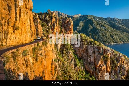 Road through the taffoni rocks, orange porphyritic granite rocks, Les Calanche de Piana, near town of Piana, Corse-du-Sud, Corsica, France - Stock Photo