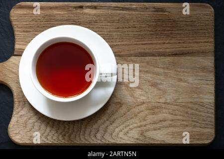 Overhead shot of clear Rooibos tea in white cup and saucer on a wooden chopping board with black slate below. - Stock Photo