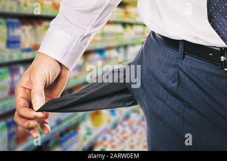 Man shows an empty pocket on the background of the store. The concept of the lack of money for purchases - Stock Photo