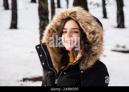 Portrait of a Young happy and beautiful teenage girl dressed in winter clothing standing at snow and smiling. Troodos mountains in Cyprus