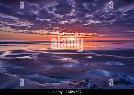 Sunrise on Bamburgh beach overlooking the Farne Islands, Bamburgh, Northumberland, england, United Kingdom