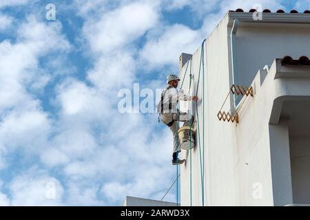 Rope access abseiler, building repairs and painter wearing full safety body harness on the side of a building - Stock Photo