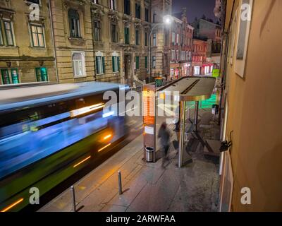 Blue bus in movement on station in Rijeka Croatia by night - Stock Photo