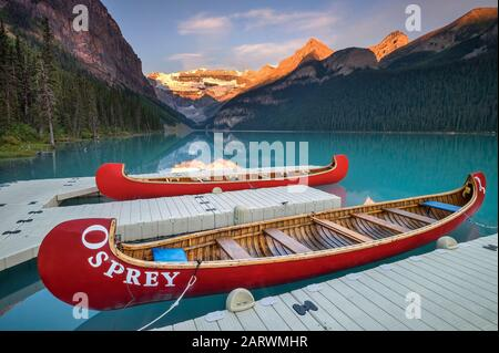 Canoes at Sunrise on Lake Louise backed by The Victoria Glacier, Lake Louise, Banff National Park, Alberta, Canada