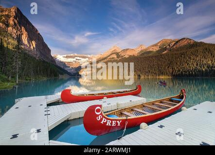 Canoe returning to jetty at Sunrise on Lake Louise backed by The Victoria Glacier, Lake Louise, Banff National Park, Alberta, Canada