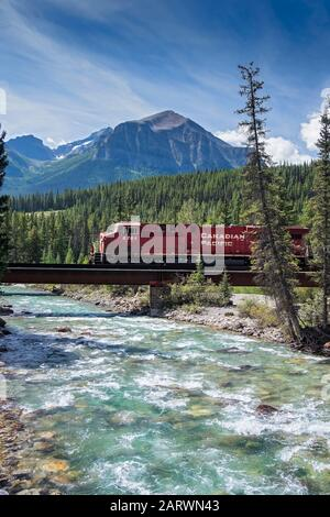 Canadian Pacific Railroad Train crossing the Bow River backed by Fairview Mountain,The Rockies, Alberta, Canada - Stock Photo