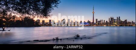 Toronto Skyline at night across Lake Ontario, from Toronto Islands Park, Toronto, Ontario, Canada - Stock Photo