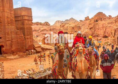 Petra, Jordan - Jan 4, 2020: Bedouins and tourists ride dromedary camels in monumental Petra, Unesco Heritage Site, a historical and archaeological - Stock Photo
