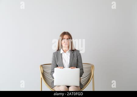 Thoughtful businesswoman with laptop sitting in armchair on light background - Stock Photo