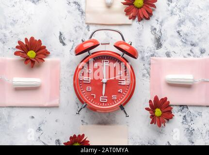 Menstrual pads with tampons and alarm clock on white background. Menstruation concept - Stock Photo