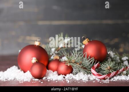 Beautiful Christmas balls with snow and fir tree branches on table - Stock Photo