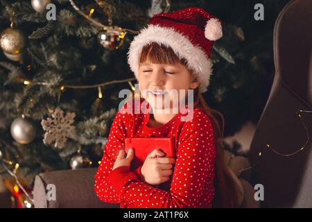 Cute little girl making a wish on Christmas eve at home - Stock Photo