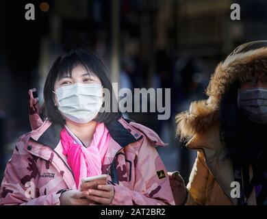 Face mask worn by a chinese tourist outside the railway station in Cambridge, England, on 30 january 2020, to prevent catching the coronavirus flu. - Stock Photo