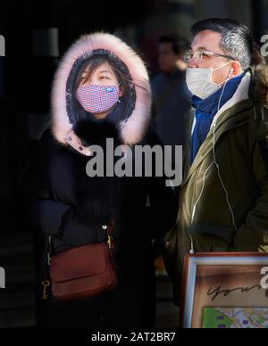 Face mask worn by chinese tourists outside the railway station in Cambridge, England, on 30 january 2020, to prevent catching the coronavirus flu. - Stock Photo