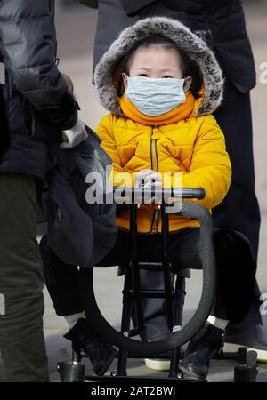 Face mask worn by a young chinese girl in Cambridge, England, on 30 january 2020, to prevent catching the coronavirus flu. - Stock Photo
